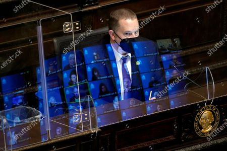 Gary Holt, who reads bills being considered in the Washington House, wears a mask as he sits behind a plexiglass shield with reflections of state representatives meeting remotely on it, at the Capitol in Olympia Wash. The House was considering a proposed new tax in Washington state on capital gains that would be imposed on the sale of stocks and bonds in excess of $250,000