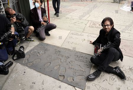"""George Chakiris, a cast member in the 1961 film """"West Side Story,"""" poses near a hand-and-footprint inscription by himself and fellow cast members Rita Moreno and Russ Tamblyn in the forecourt of the TCL Chinese Theatre, in Los Angeles. The classic Hollywood movie musical celebrates its 60th anniversary this year"""