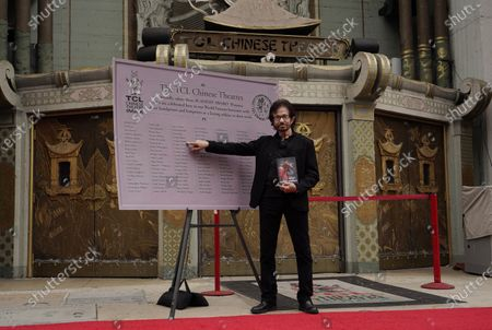 """George Chakiris, a cast member in the 1961 film """"West Side Story,"""" points to his name on a design for a new plaque honoring Oscar winners who have hand and footprints in the TCL Chinese Theatre forecourt, in Los Angeles. Chakiris won Best Supporting Actor for his performance in the classic Hollywood movie musical, which celebrates its 60th anniversary this year"""