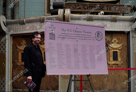 """George Chakiris, a cast member in the 1961 film """"West Side Story,"""" poses with a design for a new plaque honoring Oscar winners who have hand and footprints in the the TCL Chinese Theatre forecourt, in Los Angeles. The classic Hollywood movie musical celebrates its 60th anniversary this year"""