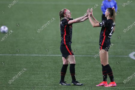 Stock Photo of Portland Thorn's Becky Sauerbrunn and Kelli Hubly celebrate their team's 2-0 win over OL Reign following an NWSL Challenge Cup soccer match, in Portland, Ore. Portland Thorns won 2-0