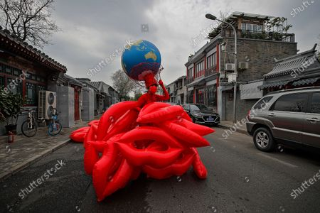 """Chinese artist and environmental activist Kong Ning unveils her latest gown collection with a theme """"Kiss the earth"""" on a street in support on Earth Day in Beijing"""