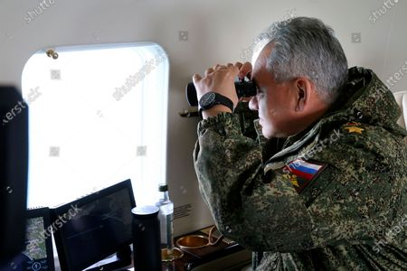 This handout photo released on by the Russian Defense Ministry Press Service shows, Russian Defense Minister Sergei Shoigu watches drills form a board of military helicopter in Crimea. The Russian military is conducting massive drills in Crimea involving dozens of navy ships and thousands of troops in a show of force amid tensions with Ukraine. The maneuvers were described as the largest since Russia annexed Ukraine's Black Sea peninsula in 2014 and threw its weight behind separatist insurgents in eastern Ukraine