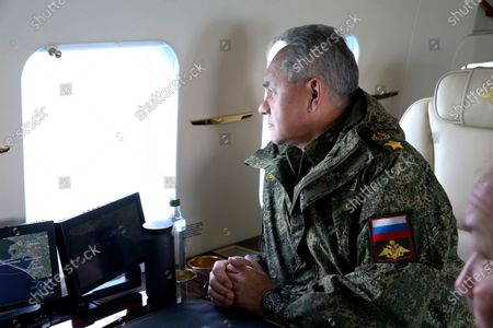 This photo released on by the Russian Defense Ministry Press Service shows, Russian Defense Minister Sergei Shoigu watches drills form a board of military helicopter in Crimea. Russia's defense minister has ordered troops back to their permanent bases after a massive exercise in Crimea that involved dozens of navy ships, hundreds of warplanes and thousands of troops in a show of force amid tensions with Ukraine. Shoigu said the troops should return to their bases by May 1, but he also ordered to keep the heavy weapons deployed to western Russia as part of the drills for another massive military exercise later this year