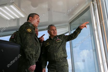 This handout photo released on by Russian Defense Ministry Press Service shows, Russian Defense Minister Sergei Shoigu, center, and General Staff Valery Gerasimov, left, talk to each other watching drills in Crimea. Russia's defense minister has ordered troops back to their permanent bases after a massive exercise in Crimea that involved dozens of navy ships, hundreds of warplanes and thousands of troops in a show of force amid tensions with Ukraine. Shoigu said the troops should return to their bases by May 1, but he also ordered to keep the heavy weapons deployed to western Russia as part of the drills for another massive military exercise later this year