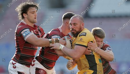 Grant Millington of Castleford is floored by Liam Byrne of Wigan Warriors and co
