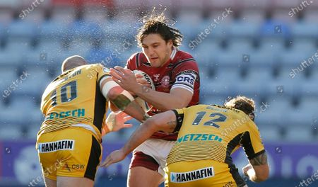 Liam Byrne of Wigan Warriors is caught by Cheyse Blair of Castleford and Grant Millington of Castleford