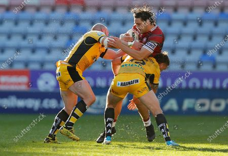 Stock Image of Liam Byrne of Wigan Warriors is caught by Cheyse Blair of Castleford and Grant Millington of Castleford