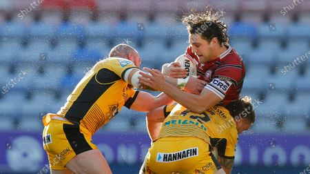 Stock Photo of Liam Byrne of Wigan Warriors is caught by Cheyse Blair of Castleford and Grant Millington of Castleford