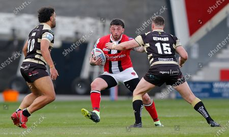 Stock Image of Oliver Roberts of Salford Red Devils tries to run through Mark Loane of Leigh Centurions and  Alex Gerrard of Leigh Centurions