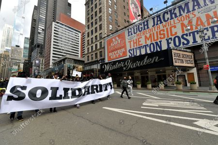 Stock Image of Demonstrators participate in the March on Broadway as it passes in front of the Winter Garden Theater, where the billboard advertises Music Man, a musical produced by Scott Rudin, who has been accused of abusive behavior.