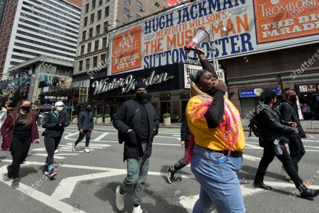 Demonstrators participate in the March on Broadway as it passes in front of the Winter Garden Theater, where the billboard advertises Music Man, a musical produced by Scott Rudin, who has been accused of abusive behavior.
