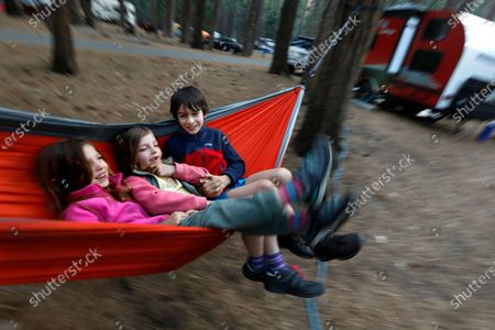 YOSEMITE NATIONAL PARK-APRIL 19, 2021-Charlotte Briggs, left, age 6, Grace Briggs, age 7, and Samuel Briggs, age 9, camp in Yosemite with their parents Tim and Francesca Briggs, of Brentwood, (East Bay) California, on Sunday April 18, 2021. Yosemite National Park is open at a reduced capacity, and will require reservations to drive into the park starting on May 21, 2021. (Carolyn Cole / Los Angeles Times)