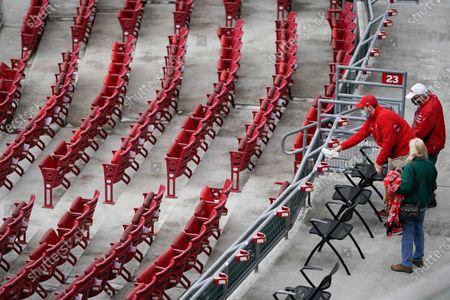 An usher wipes down seats before a baseball game between the Cincinnati Reds and the Arizona Diamondbacks at Great American Ball Park in Cincinnati