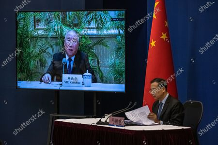 Ma Zhaoxu (R), a Chinese vice-minister of Foreign Affairs, sits next to a screen showing Xie Zhenhua, China's Special Envoy for Climate Change, speaking during a media briefing on Chinese President Xi Jinping's attendance at virtual international Leaders Summit on Climate, at the Ministry of Foreign Affairs, in Beijing, China, 22 April 2021. Around 40 international leaders attended the summit called by US President Biden. The meeting is intended to underline the urgency and economic benefits of stronger climate action on the road to the United Nations Climate Change Conference (COP26) in Glasgow in November 2021.