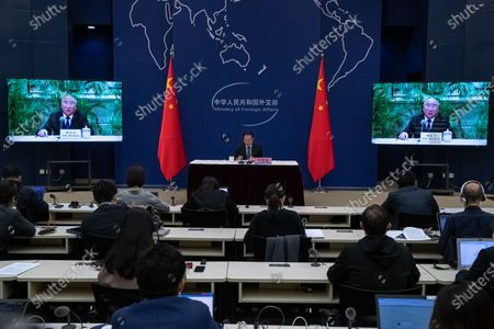 Ma Zhaoxu (C), a Chinese vice-minister of Foreign Affairs, sits next to screenw showing Xie Zhenhua, China's Special Envoy for Climate Change, speaking during a media briefing on Chinese President Xi Jinping's attendance at virtual international Leaders Summit on Climate, at the Ministry of Foreign Affairs, in Beijing, China, 22 April 2021. Around 40 international leaders attended the summit called by US President Biden. The meeting is intended to underline the urgency and economic benefits of stronger climate action on the road to the United Nations Climate Change Conference (COP26) in Glasgow in November 2021.