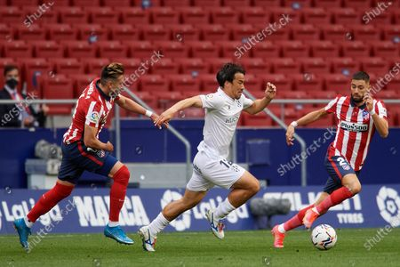 Shinji Okazaki of Huesca and Hector Herrera and Yannick Carrasco of Atletico Madrid compete for the ball during the La Liga Santander match between Atletico de Madrid and SD Huesca at Estadio Wanda Metropolitano on April 22, 2021 in Madrid, Spain. Sporting stadiums around the Spain remain under strict restrictions due to the Coronavirus Pandemic as Government social distancing laws prohibit fans inside venues resulting in games being played behind closed doors.