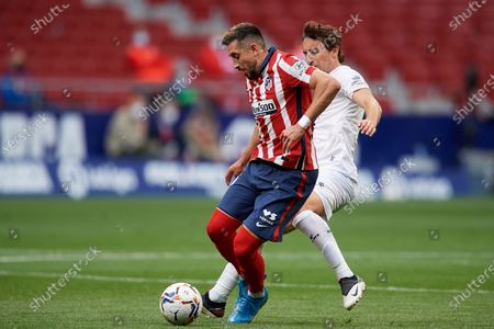 Hector Herrera of Atletico Madrid and Pedro Mosquera of Huesca compete for the ball during the La Liga Santander match between Atletico de Madrid and SD Huesca at Estadio Wanda Metropolitano on April 22, 2021 in Madrid, Spain. Sporting stadiums around the Spain remain under strict restrictions due to the Coronavirus Pandemic as Government social distancing laws prohibit fans inside venues resulting in games being played behind closed doors.