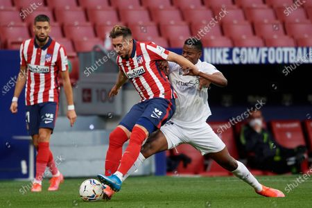 Hector Herrera of Atletico Madrid and Idrissa Doumbia of Huesca compete for the ball during the La Liga Santander match between Atletico de Madrid and SD Huesca at Estadio Wanda Metropolitano on April 22, 2021 in Madrid, Spain. Sporting stadiums around the Spain remain under strict restrictions due to the Coronavirus Pandemic as Government social distancing laws prohibit fans inside venues resulting in games being played behind closed doors.