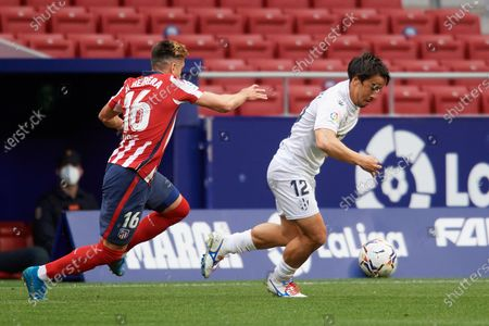 Shinji Okazaki of Huesca and Hector Herrera of Atletico Madrid compete for the ball during the La Liga Santander match between Atletico de Madrid and SD Huesca at Estadio Wanda Metropolitano on April 22, 2021 in Madrid, Spain. Sporting stadiums around the Spain remain under strict restrictions due to the Coronavirus Pandemic as Government social distancing laws prohibit fans inside venues resulting in games being played behind closed doors.