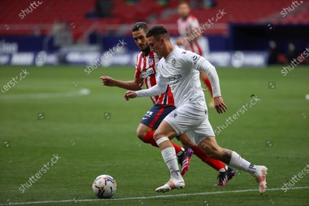 Atletico's midfielder Koke Resurreccion (L) vies for the ball against Huesca's Dani Escriche (R) during the Spanish LaLiga soccer match between Atletico de Madrid and SD Huesca at Wanda Metropolitano stadium in Madrid, Spain, 22 April 2021.