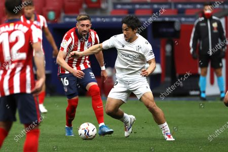 Atletico's midfielder Hector Herrera (L) vies for the ball against Huesca's striker Shinji Okazaki (R) during the Spanish LaLiga soccer match between Atletico de Madrid and SD Huesca at Wanda Metropolitano stadium in Madrid, Spain, 22 April 2021.