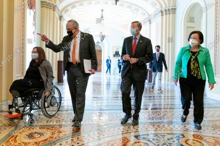 From left, Sen. Tammy Duckworth, D-Ill., Senate Majority Leader Chuck Schumer of N.Y., Sen. Richard Blumenthal, D-Conn., and Sen. Mazie Hirono, D-Hawaii, right, walk to a news conference after the Senate passes a COVID-19 Hate Crimes Act on Capitol Hill, in Washington