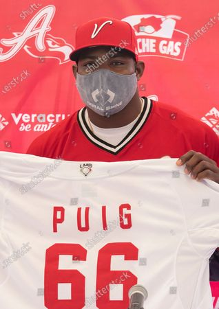 Stock Photo of Cuban baseball player Yasiel Puig poses for a photo with his jersey during his media presentation after signing with El Aguila de Veracruz in Veracruz, Mexico, . The 30-year-old player will join the team in the next season of the Mexican League