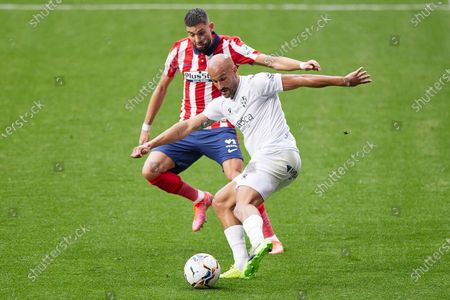 Mikel Rico of SD Huesca and Yannick Carrasco of Atletico de Madrid