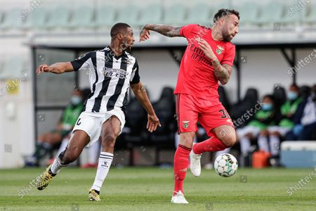 Portimonense player Beto (L)  fights for the ball with Benfica player Nicolas Otamendi (R)  during the Portuguese First League soccer match between Portimonense and Benfica held at Municipal de Portimao stadium in Portimao, Portugal, 22 April 2021.