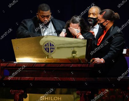 Stock Photo of Aubrey Wright and the Reverend Al Sharpton and a family member comfort Katie Wright as she delivers remarks during the funeral for 20 year old Daunte Wright who was shot and killed by police officer Kimberly Ann Potter during a traffic stop and attempted arrest in Brooklyn Center