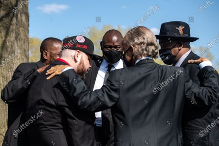 Reverend Al Sharpton says a prayer with Daunte's father, Aubrey Wright and brother, Damik Wright during Daunte's burial at Lakewood Cemetery