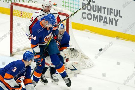 New York Islanders' Scott Mayfield (24) defends against Washington Capitals center Nicklas Backstrom (19) as Islanders goaltender Semyon Varlamov (40) makes a save during the second period of an NHL hockey game, in Uniondale, N.Y