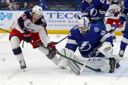 Tampa Bay Lightning goaltender Curtis McElhinney (35) makes a save against Columbus Blue Jackets' Eric Robinson during the first period of an NHL hockey game, in Tampa, Fla
