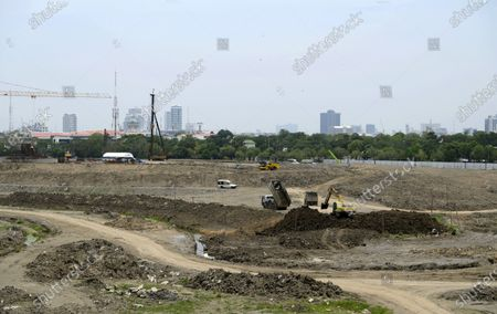 Stock Image of Earth moving equipment seen at the Racecourse. Bangkok's former horse race track the Nang Loeng Racecourse, otherwise known as the Royal Bangkok Turf Club, which was established on Dec 18, 1916, during the reign of King Rama VI. The race track and buildings were returned to the Crown Property Bureau in 2018 after 102 years of operation and was subsequently demolished. Work is now underway to convert the present location of 79 acres of land, equivalent to 60 football fields, into a public park, with a monument to honour the late King Bhumibol Adulyadej.