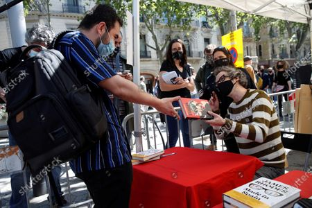 British pianist and writer James Rhodes (R) signs books at a bookshop stand in Barcelona, Spain, on occasion of Sant Jordi celebrations, 23 April 2021.  Catalonia celebrates its patron saint, Sant Jordi (known in English as St. George) every year on 23 April, which also coincides with World Book Day, by gifting roses and books to their loved ones.