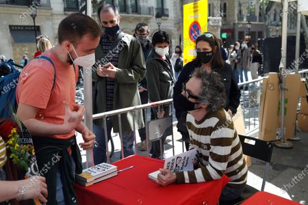 Stock Picture of British pianist and writer James Rhodes (R) signs books at a bookshop stand in Barcelona, Spain, on occasion of Sant Jordi celebrations, 23 April 2021.  Catalonia celebrates its patron saint, Sant Jordi (known in English as St. George) every year on 23 April, which also coincides with World Book Day, by gifting roses and books to their loved ones.