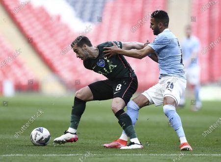 Harry Winks of Tottenham Hotspur holds off Riyad Mahrez of Manchester City