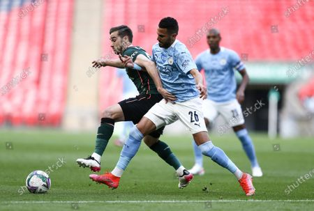 Riyad Mahrez of Manchester City tackles Harry Winks of Tottenham Hotspur