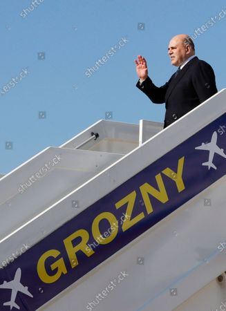 Russian Prime Minister Mikhail Mishustin gestures as he steps down from the plane upon his arriving at an airport outside the Chechen capital of Grozny, Russia, . During his visit Mishustin has to meet with Chechnya's regional leader Ramzan Kadyrov