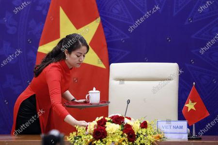 A girl prepares drink for Vietnamese President Nguyen Xuan Phuc at the virtual Leaders summit on climate in Hanoi, Vietnam, 23 April 2021. The summit which is hosted by the US from 22 to 23 April.