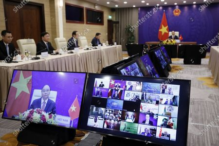 Vietnamese President Nguyen Xuan Phuc (on screen, left) attends the virtual Leaders summit on climate in Hanoi, Vietnam, 23 April 2021. The summit which is hosted by the US from 22 to 23 April.