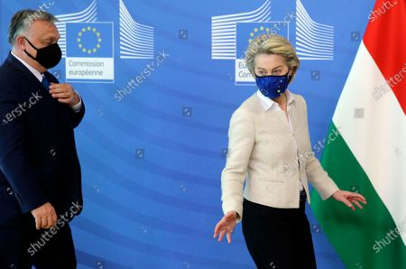 Hungarian Prime Minister Viktor Orban, left, walks with European Commission President Ursula von der Leyen prior to a formal greeting at EU headquarters in Brussels
