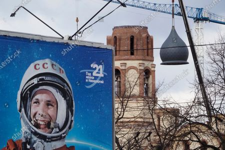 Crane mounts a dome on an Orthodox church under construction in St. Petersburg, Russia, with a poster depicting a portrait of Yuri Gagarin, hanged during the celebration of the 60th anniversary of Russia's Yuri Gagarin's first manned flight into space, in the foreground