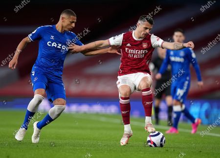 Arsenal's Granit Xhaka, right, duels for the ball with Everton's Richarlison during the English Premier League soccer match between Arsenal and Everton at the Emirates stadium in London