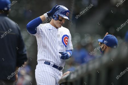 Chicago Cubs' Anthony Rizzo celebrates with manager David Ross at the dugout after hitting a solo home run during the second inning of a baseball game against the Milwaukee Brewers, in Chicago