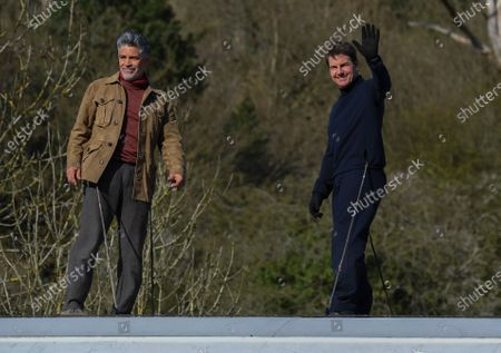 Tom Cruise alongside Esai Morales waves from a train during the filming of Mission Impossible 7 in Levisham, North Yorkshire