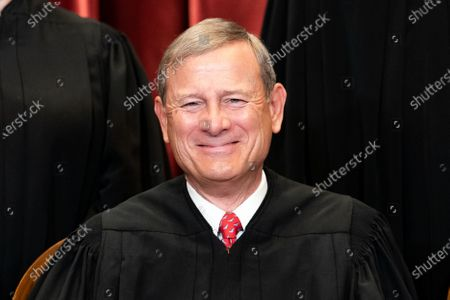 Chief Justice of the United States John G. Roberts, Jr. sits during a group photo of the Justices at the Supreme Court in Washington, DC.