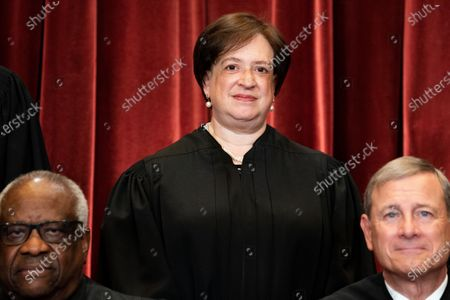 Associate Justice of the Supreme Court Elena Kagan, with Associate Justice of the Supreme Court Clarence Thomas and Chief Justice of the United States John G. Roberts, Jr. in front of her, stands during a group photo of the Justices at the Supreme Court in Washington, DC.
