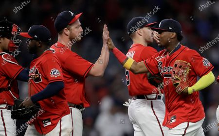 Atlanta Braves' Ronald Acuna Jr., right, celebrate the win over the Arizona Diamondbacks with pitcher Will Smith at the end of a baseball game, in Atlanta